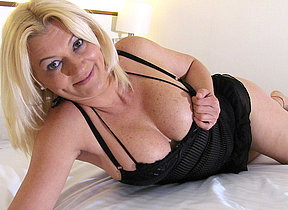 Blonde mature whore playing with herself on the bed