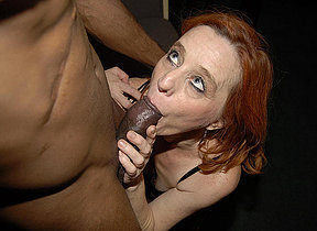 Red mature slut munching on a big black dick