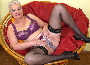 Horny mature hussy playing in her chair